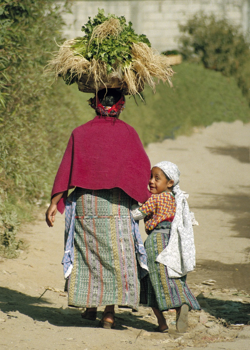 Women carrying produce in a basket on her head holds the hand of a small child next to here