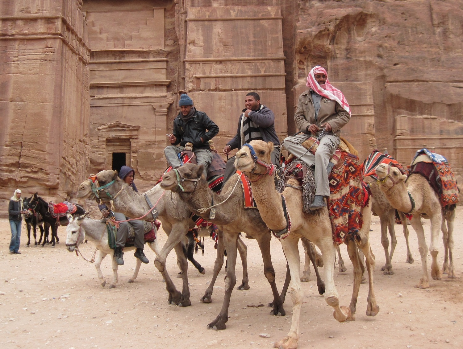 Three men riding camels in front of an ancient building in the desert