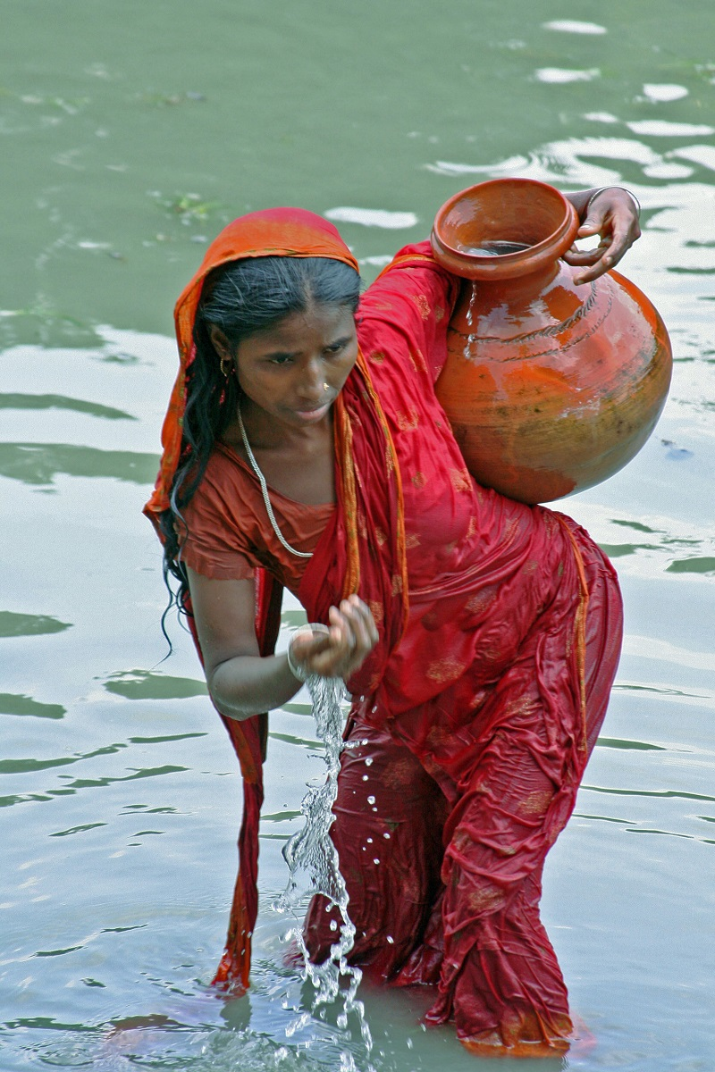 Woman wearing colorful clothes and collecting water into a jug.