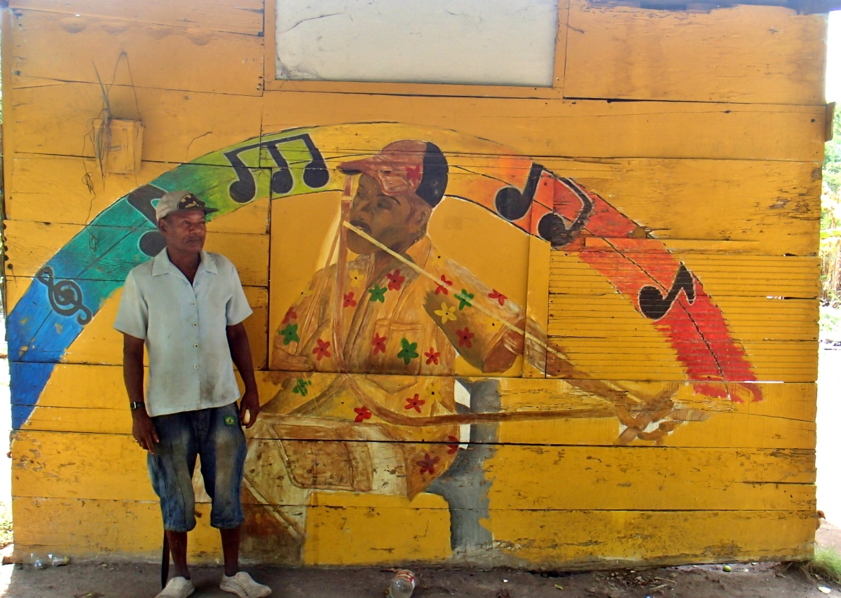 man standing in front of a music-themed mural
